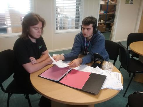 James with his carer Tom, filing some supplier invoices